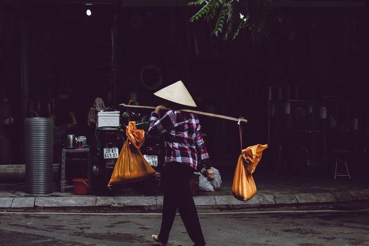 Vietnamese Woman carrying bags on a bamboo stick. One Person People Vietnam Travel ASIA