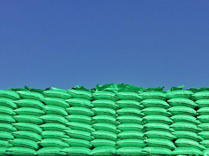 Low angle view of green stacked sacks against clear blue sky