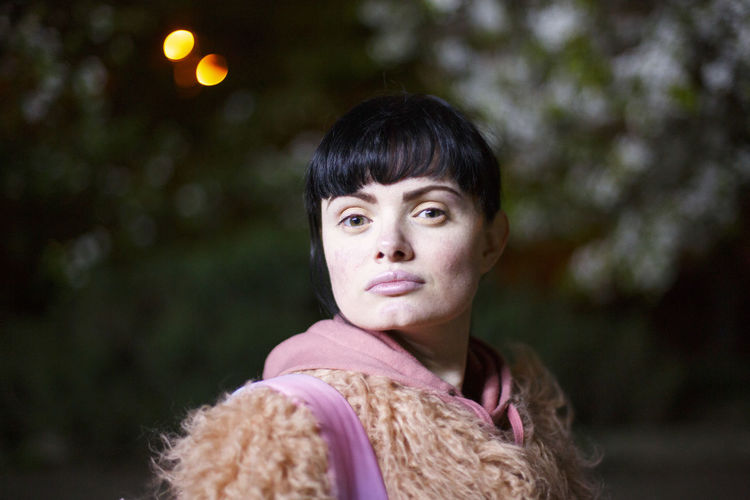 Portrait of woman wearing fur coat against trees