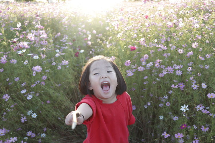 High Angle Portrait Of Smiling Girl Standing Amidst Plants