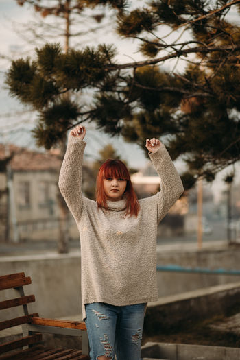 One Person Tree Human Arm Real People Arms Raised Winter Casual Clothing Front View Standing Warm Clothing Lifestyles Young Adult Emotion Leisure Activity Women Focus On Foreground Adult Happiness Outdoors Hairstyle