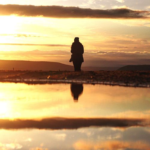 Silhouette of man in water at sunset