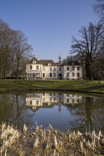 View of the house in Baak reflecting in the canal near the village of the same name in the Dutch region Achterhoek Architecture Bare Tree Building Exterior Built Structure Day Detached House Grass House Luxury No People Outdoors Reflection Residential Building Sky Tree Water