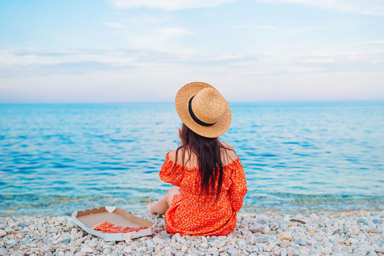 Rear view of woman wearing hat sitting at beach