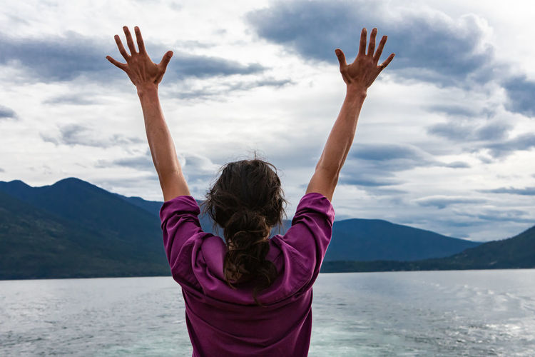 Rear view of woman with arms raised in mountains against sky