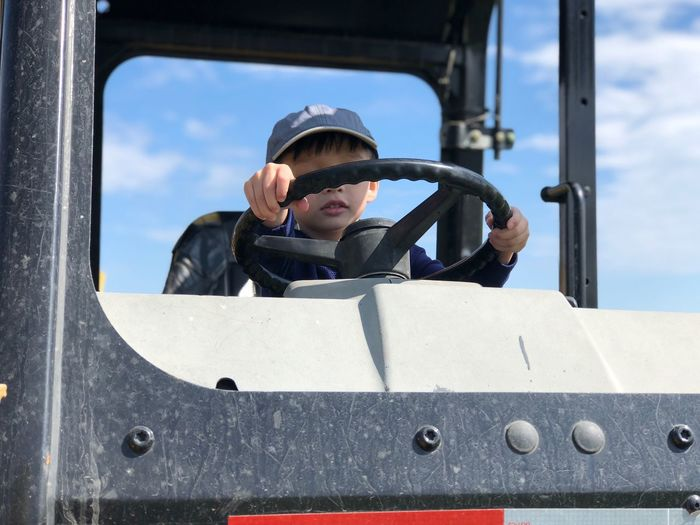 Low angle view of boy holding steering wheel of vehicle against sky