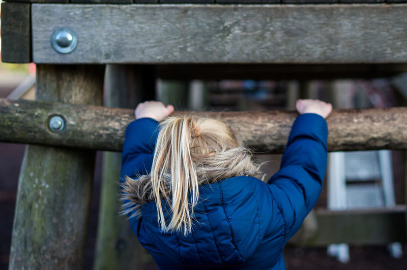Blond Hair Blue Child Childhood Climbing Day Girl Human Body Part Jacket One Person Outdoors People Playground Playing Rear View Waist Up Wood Wood - Material Wooden