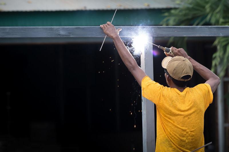 Rear View Of Man Welding Metal At Workshop