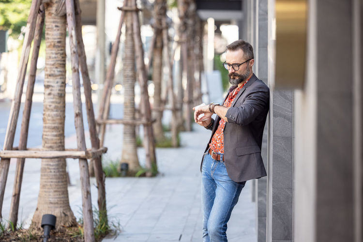 Attractive young businessman in stylish suit looking at watch in business district outdoors person