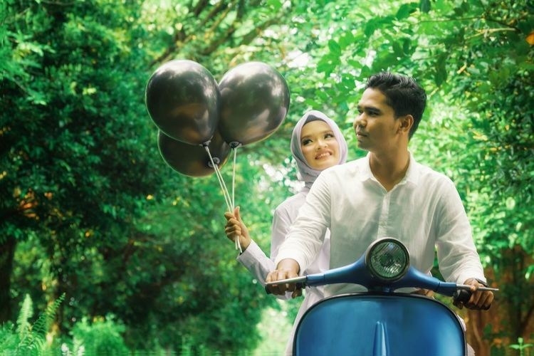 People Riding On Motor Scooter With Balloons Amidst Trees
