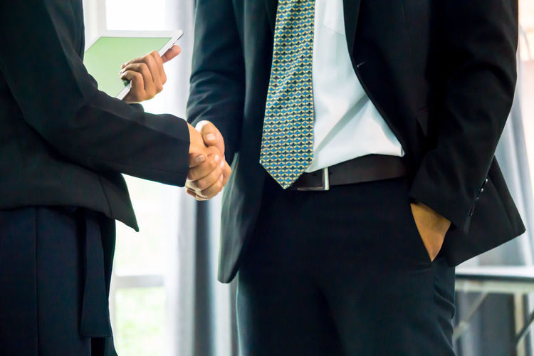 Midsection of business people giving handshake while standing in office