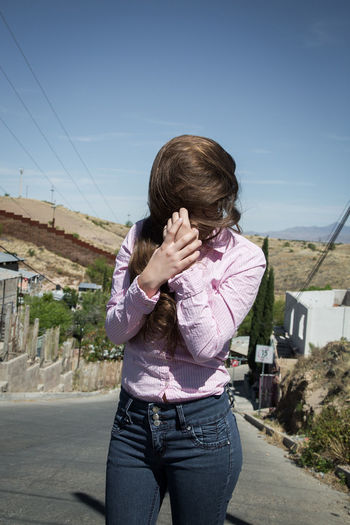 Woman Covering Face With Hair On Street Against Sky During Sunny Day