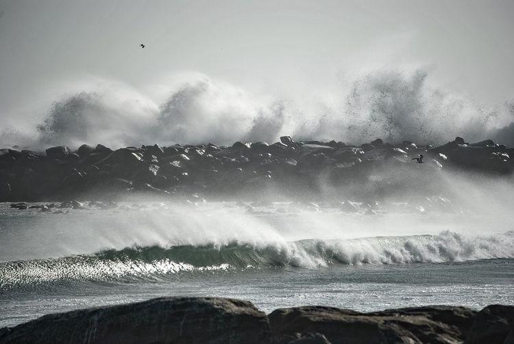 Waves Splashing On Groyne In Sea Against Sky