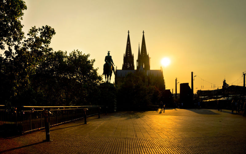 Sunset at Cologne viewing Dom Cathedral Köln Kölner Dom Architecture Art And Craft Building Building Exterior Built Structure City Dom Cathedral Human Representation Male Likeness Men Nature Outdoors Plant Real People Religion Representation Sculpture Shillouette Sky Statue Sunset Travel Destinations Tree