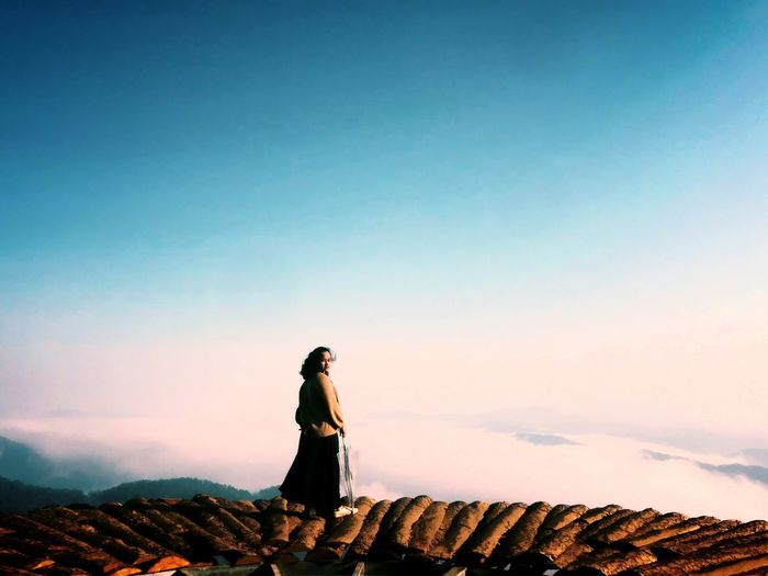 Full length of woman standing on observation point against sky during sunset