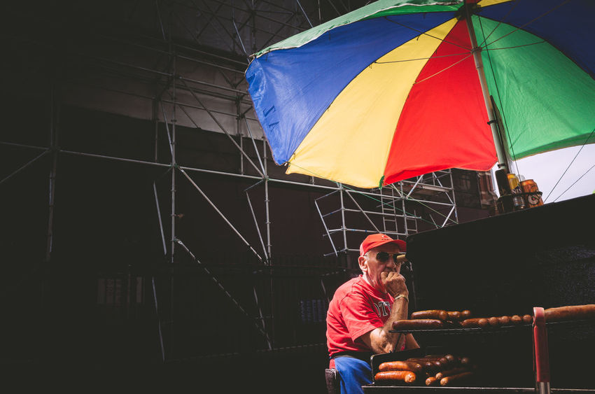 Casual Clothing Day Lifestyles Multicolored One Person Outdoors People Real People rule of thirds Sitting Umbrella