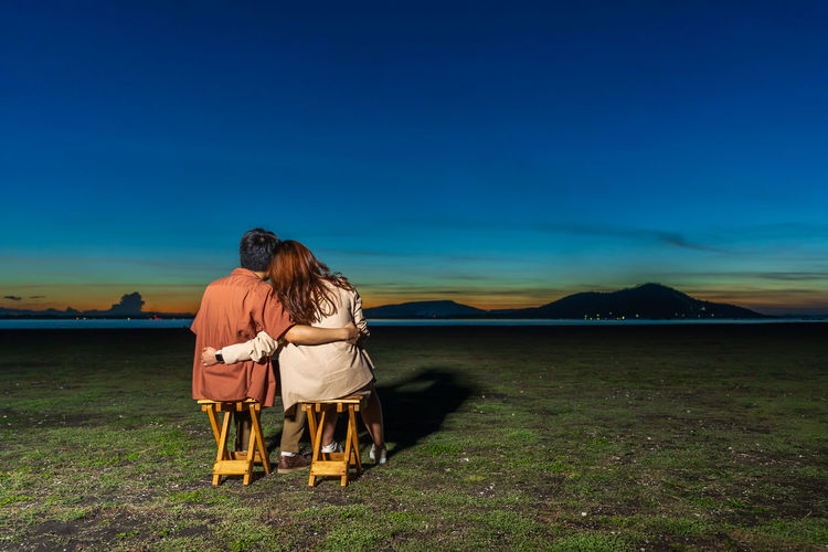 Rear view of couple sitting on seat