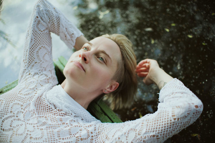 High angle view of thoughtful woman while lying outdoors