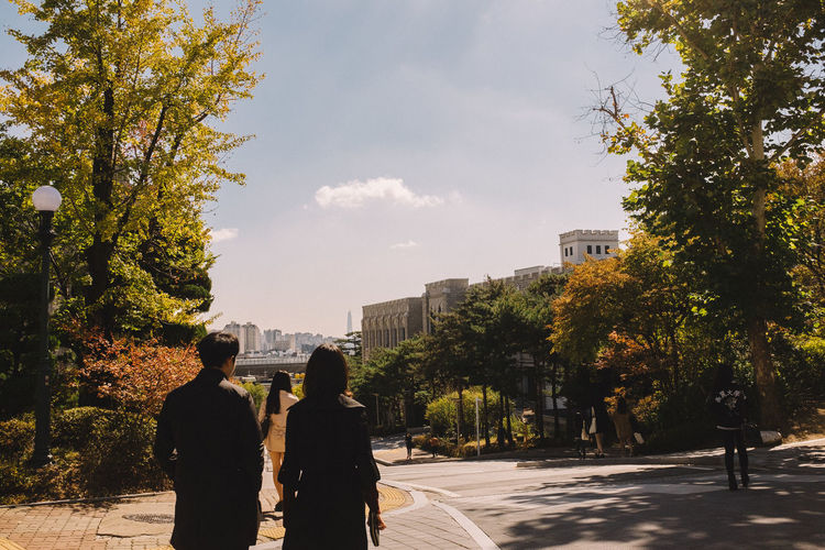 Rear view of people walking at korea university campus during autumn
