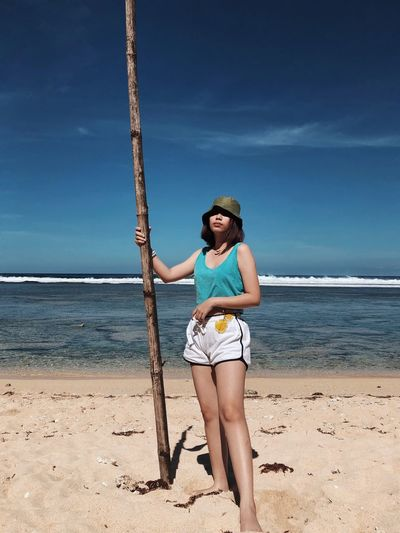 Full length of young woman standing at beach against sky during summer