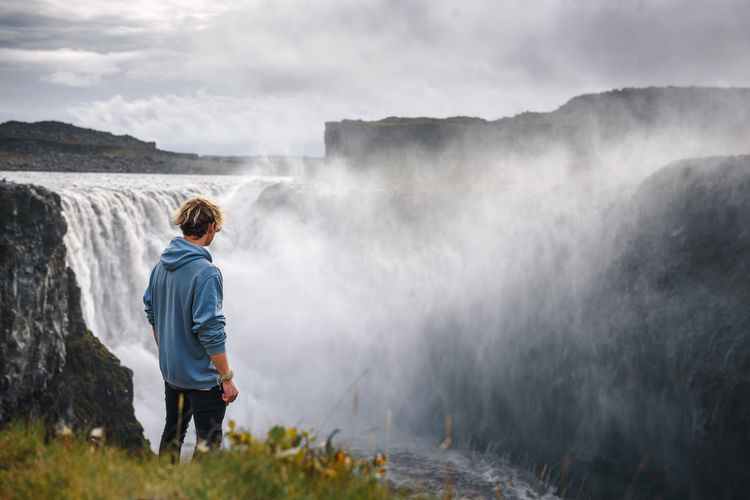 Rear view of man looking at waterfall against mountain