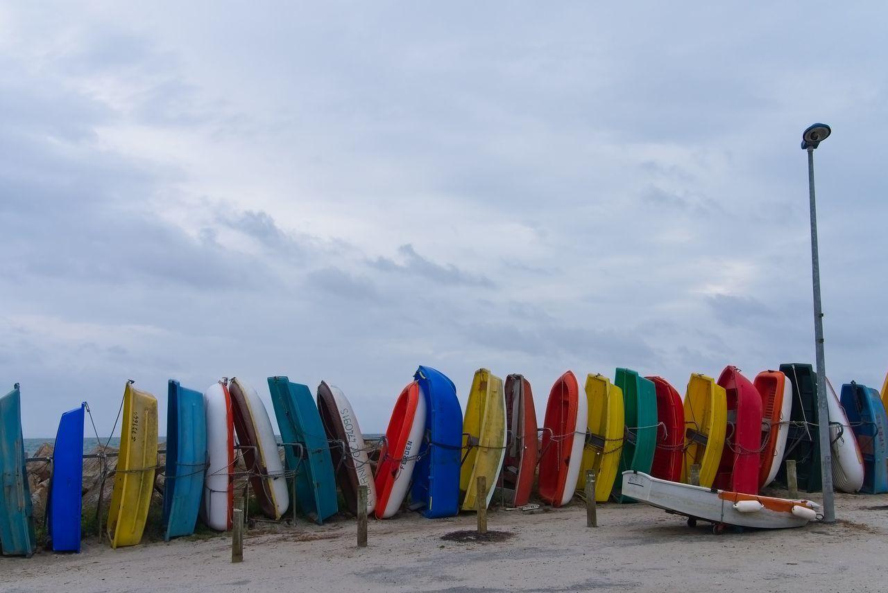 Multi Colored Umbrellas On Beach Against Sky