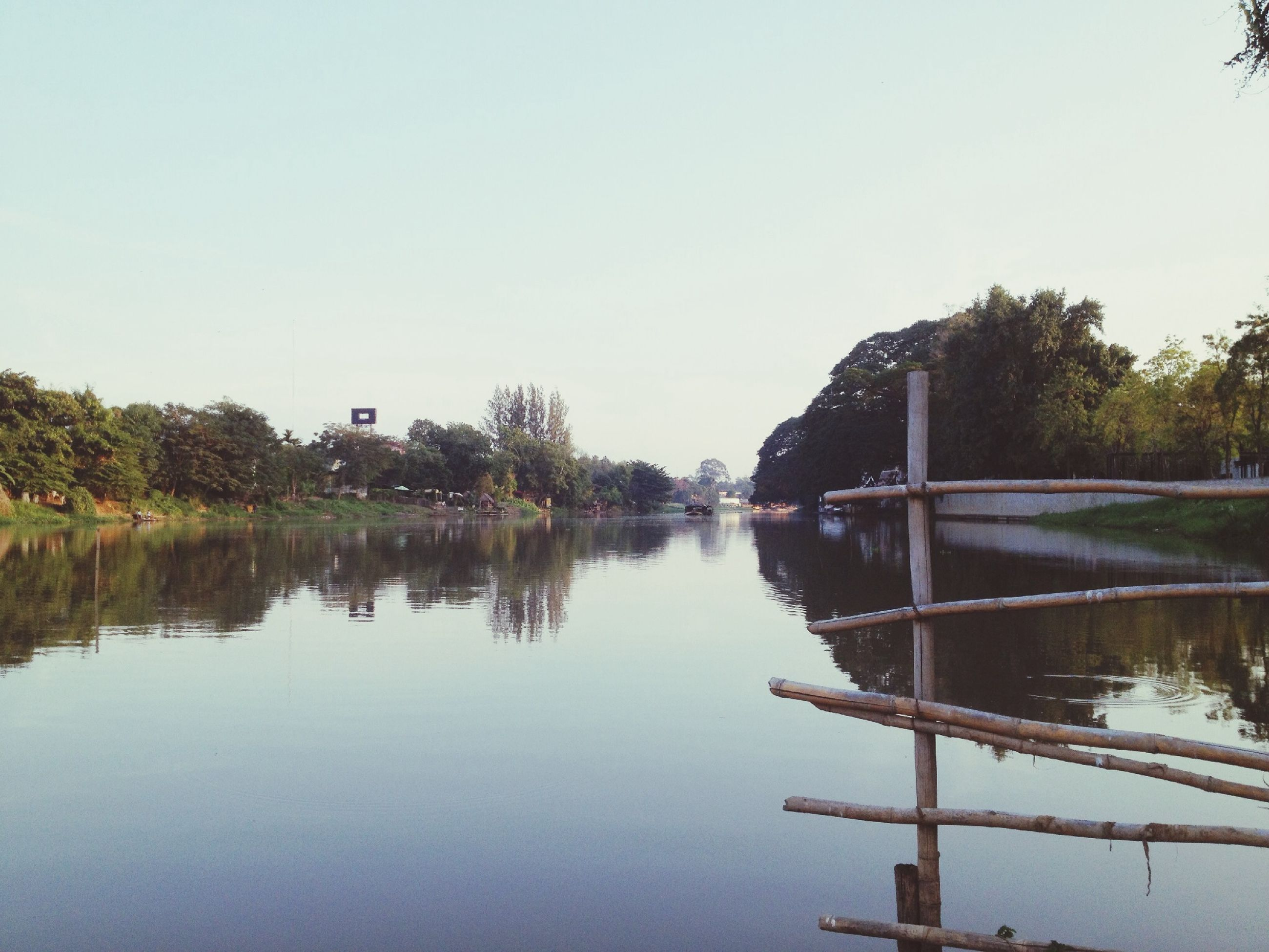 water, clear sky, reflection, lake, tree, waterfront, copy space, tranquility, built structure, tranquil scene, river, architecture, nature, scenics, beauty in nature, standing water, calm, day, outdoors, no people