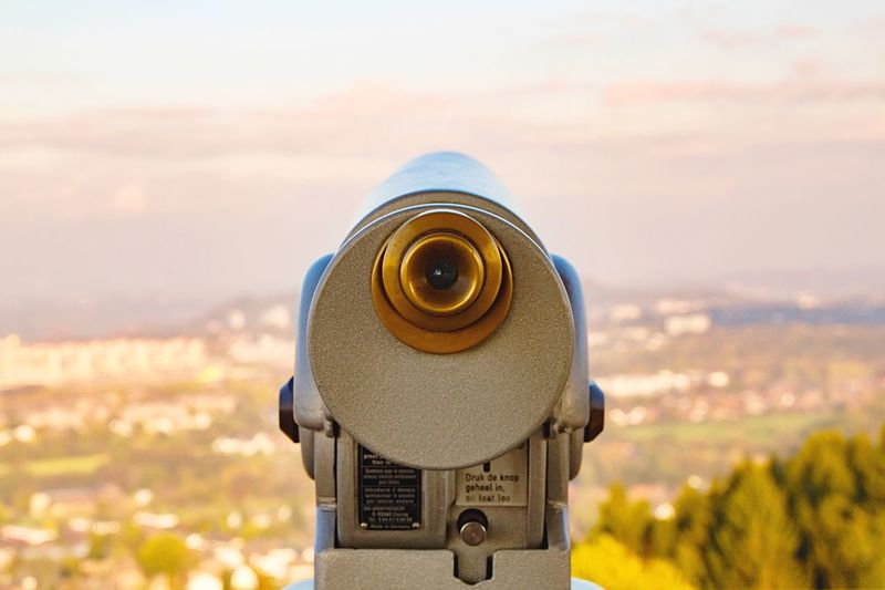 Close-Up Of Coin-Operated Binoculars By Cityscape Against Sky