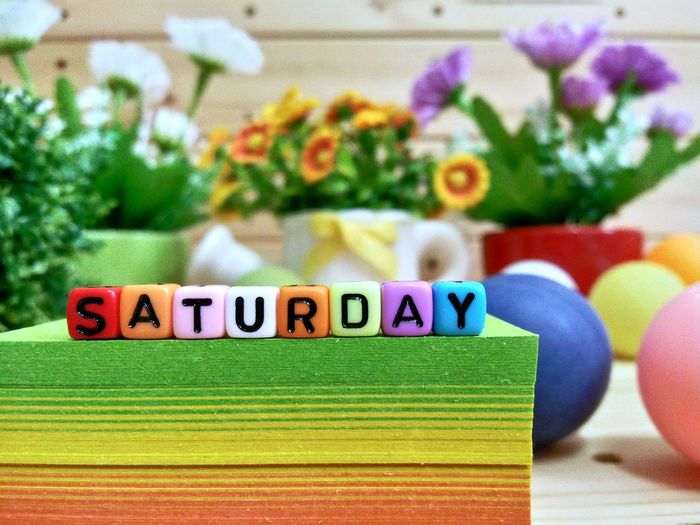 Close-up of colorful blocks with saturday text on stacked papers over table