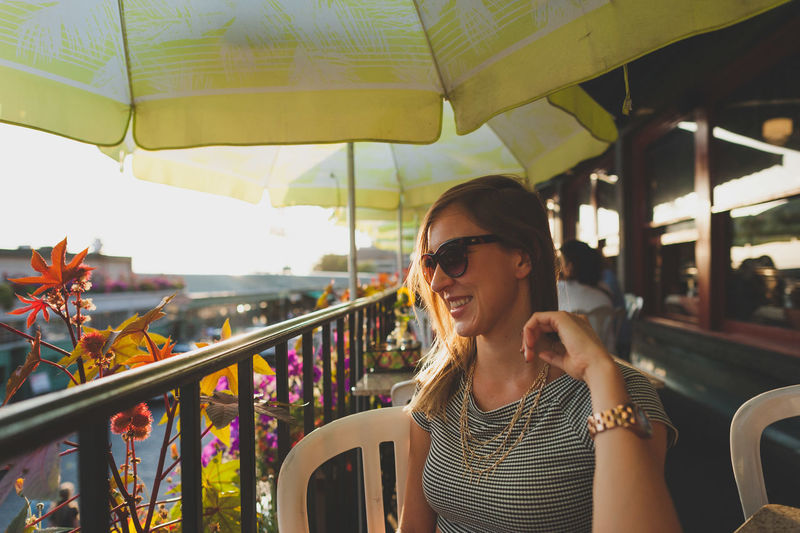 Happy young woman sitting by railing in restaurant