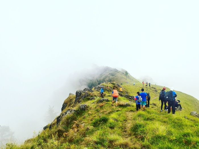 People walking on mountain during foggy weather