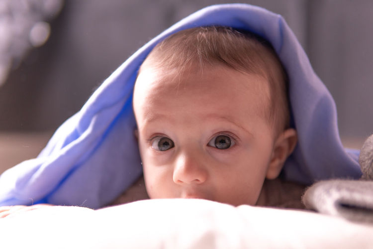 Close-up portrait of cute baby lying down on bed