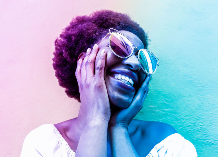 Close-up of smiling woman wearing sunglasses against wall