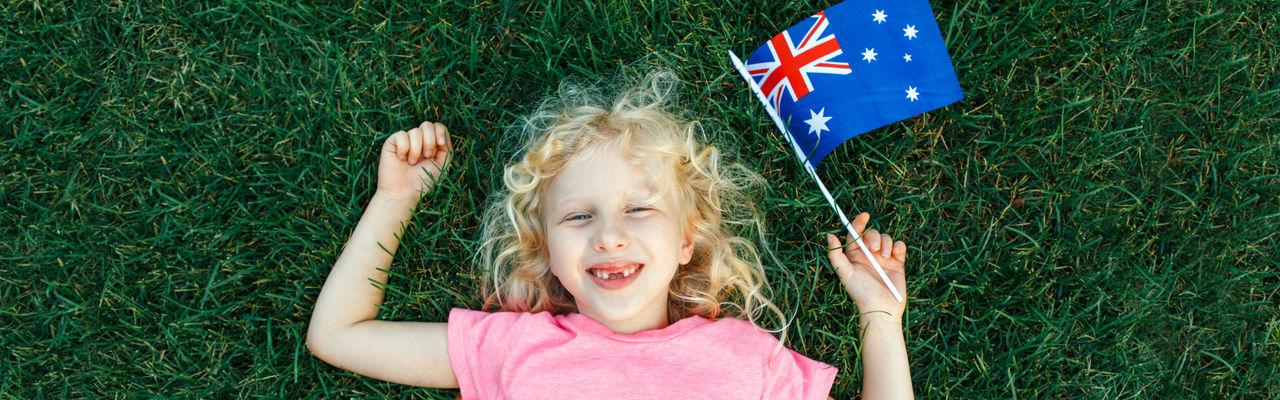 High angle portrait of cute girl holding australian flag lying on grass