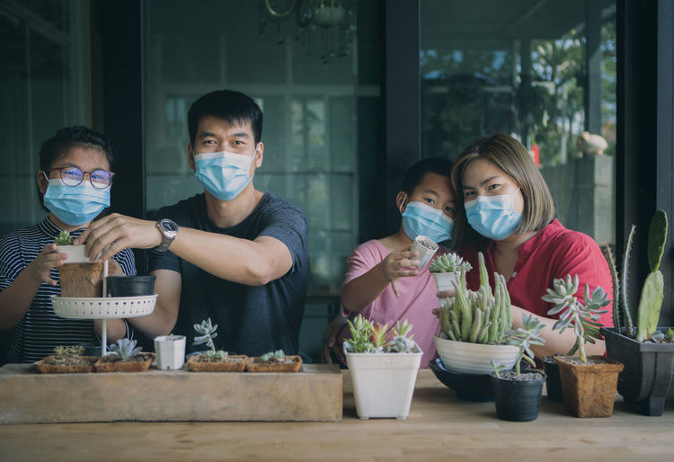 Portrait of cheerful family wearing mask holding succulent plants on table