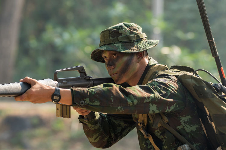 Soldier holding gun outdoors