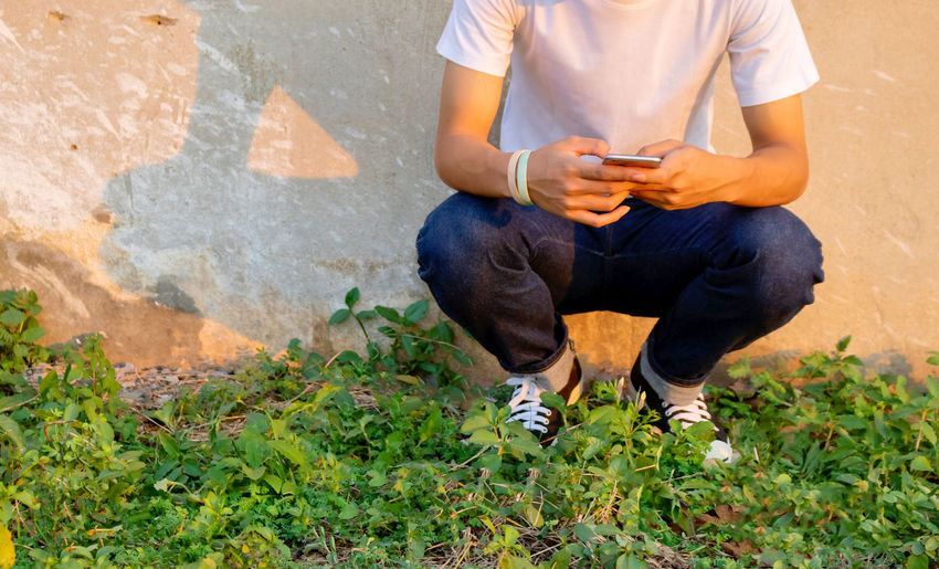 Low section of man using mobile phone while crouching on plants