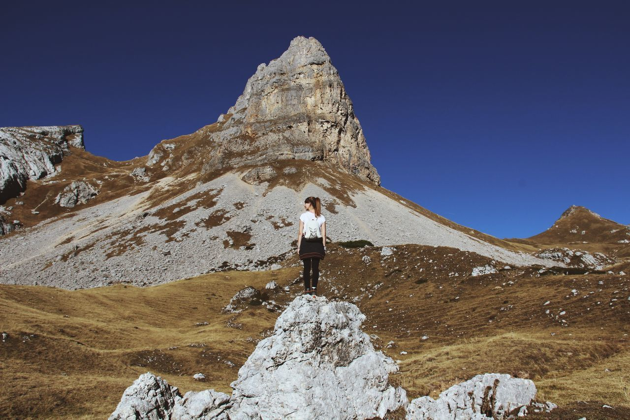 Full length of woman standing on rock against mountain