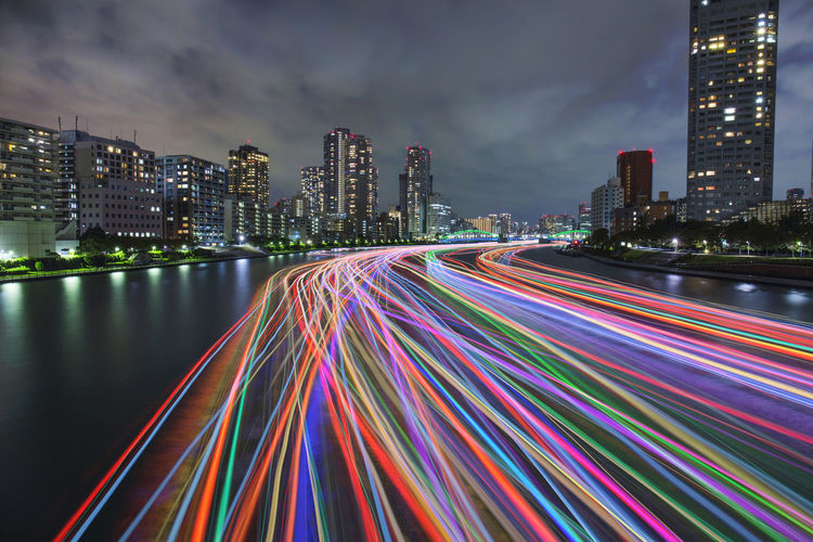 Light trails on city by buildings against sky at night