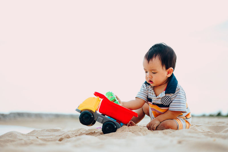 Cute boy playing with toy on sand