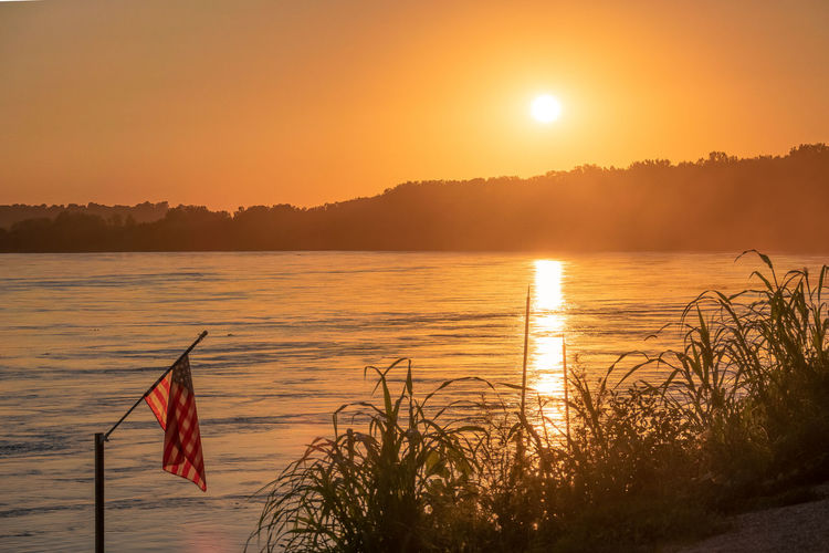 Beauty In Nature Flag Idyllic Lake Nature No People Non-urban Scene Orange Color Outdoors Plant Reflection Scenics - Nature Sky Sun Sunlight Sunset Tranquil Scene Tranquility Water