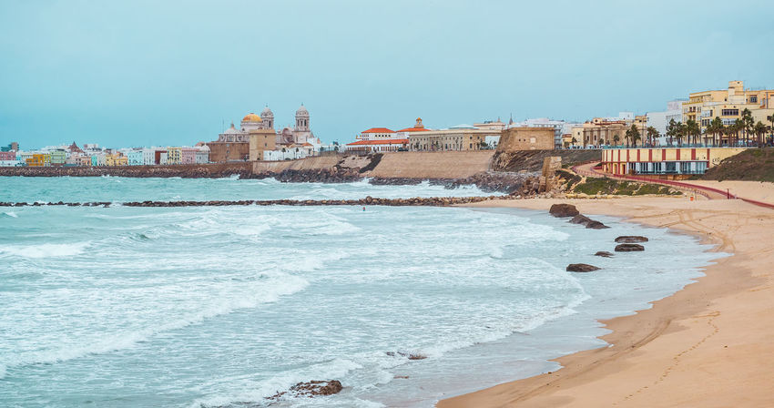 Cadiz coastline in winter. Southwestern Spain Ancient Architecture Andalucía Atlantic Ocean Blue Sky Breaking Waves Breakwater City Coast Coastline Cádiz, Spain Day Europe Landscape Malaga Nature Ocean Outdoors Picturesque Sandy Beach Sea Shoreline Skyline SPAIN Stormy Weather Town