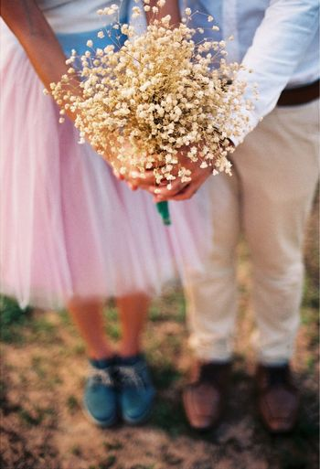 Low Section Of Couple Holding Flower While Standing On Field