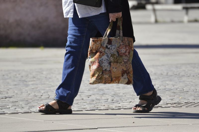 Low section of person carrying tote bag on footpath