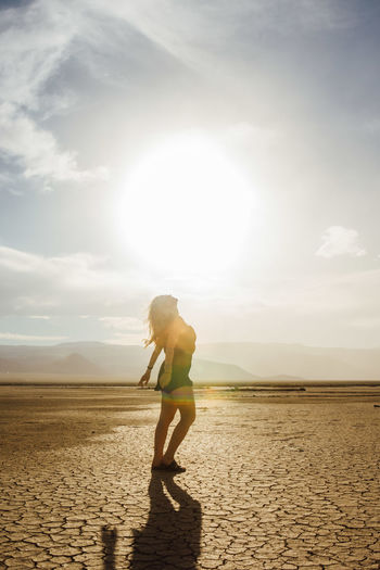 Side view of young woman standing at desert against sky during sunny day