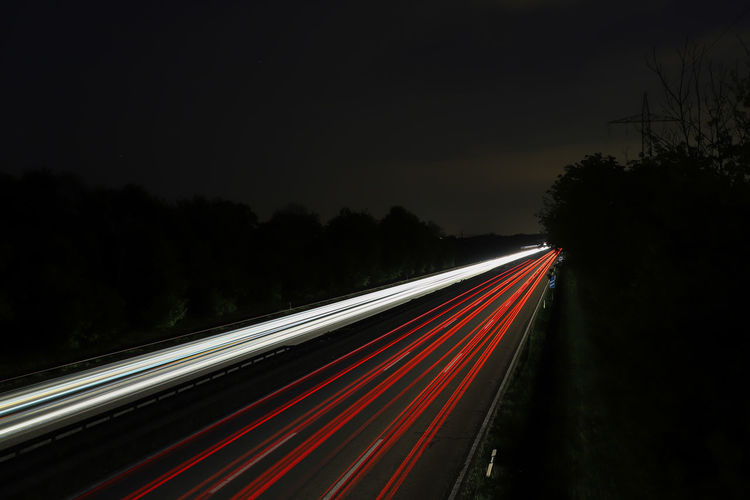 Blurred Motion Copy Space Highway Illuminated Light Trail Long Exposure Motion Multiple Lane Highway Nature Night No People Outdoors Plant Red Road Sky Speed Tail Light The Way Forward Traffic Transportation Tree Vehicle Light