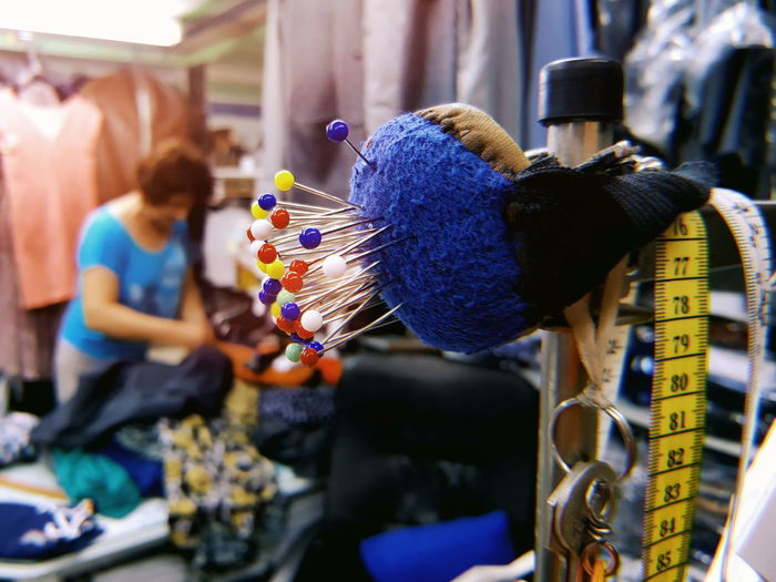 Close-up of pin cushion on pole at tailor shop