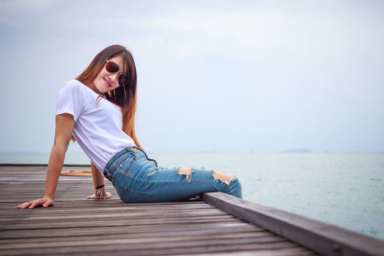 Young woman wearing sunglasses sitting on pier by sea against sky