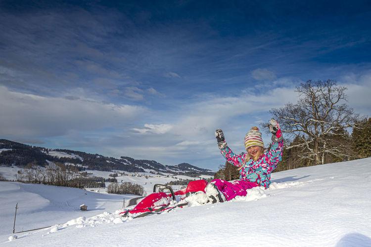 Full length portrait of girl sitting on snow covered land during winter