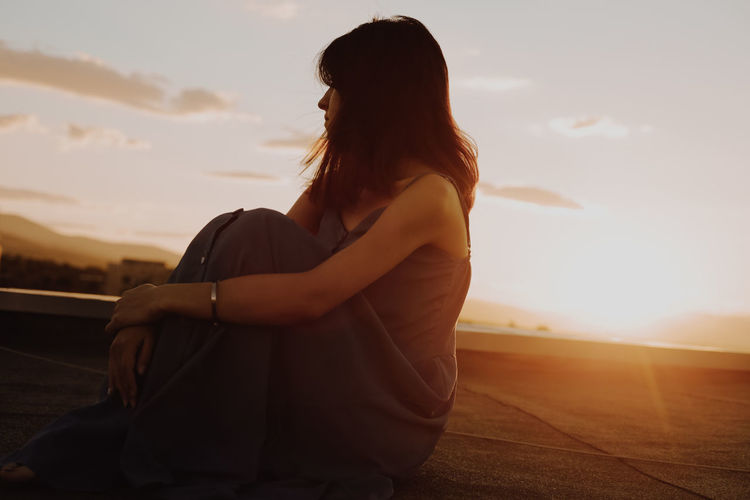 Mature Woman Sitting On Terrace Against Sky During Sunset